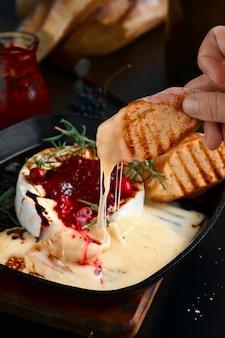 Queso camembert al horno con salsa de arándanos y romero en una sartén