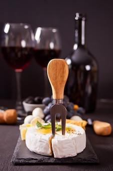Queso camembert brie en el tablero, dos vasos y una botella de vino tinto