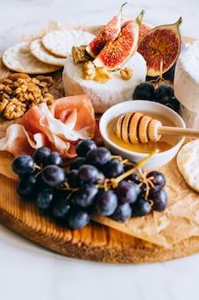 Queso camembert, higos, jamón, miel y uvas. plato de queso sobre fondo de mármol