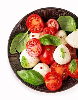 Queso camembert redondo con tomates cherry y albahaca en un plato oscuro