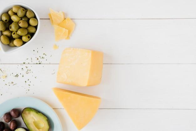 Queso cheddar con aceitunas verdes y rebanada de aguacate en mesa de madera blanca
