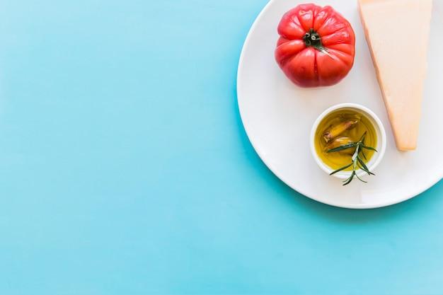 Queso cheddar triangular con tomate rojo y guante de ajo y aceite de hierbas de romero en un plato