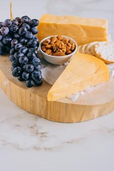 Queso cheddar, uvas, nueces, miel y galleta en tabla de madera sobre mármol