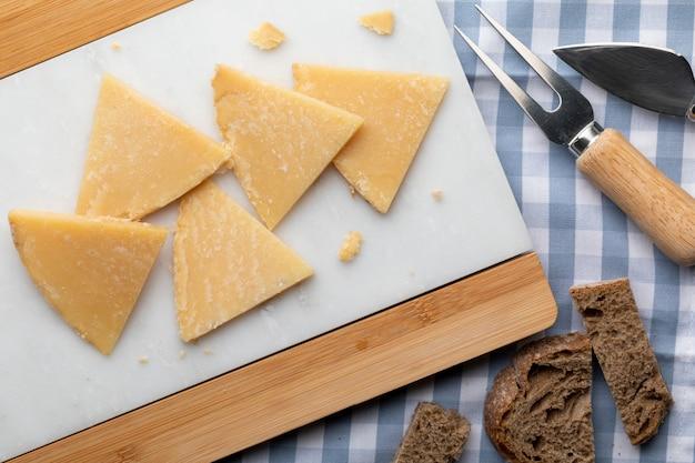 Queso curado de oveja. cortar en trozos de mármol blanco y pan. tenedor y cuchillo para queso. vista superior.