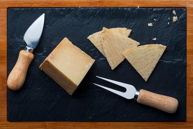 Queso curado de oveja. cortar en trozos sobre tabla de madera y pizarra negra. tenedor y cuchillo para queso. vista superior.