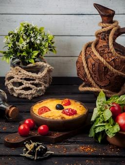 Queso derretido cubierto con rodajas de tomate y aceitunas en una sartén de cerámica