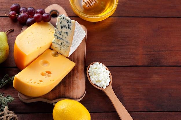Queso duro, queso azul y requesón sobre tabla de madera. diferentes tipos de queso y miel.