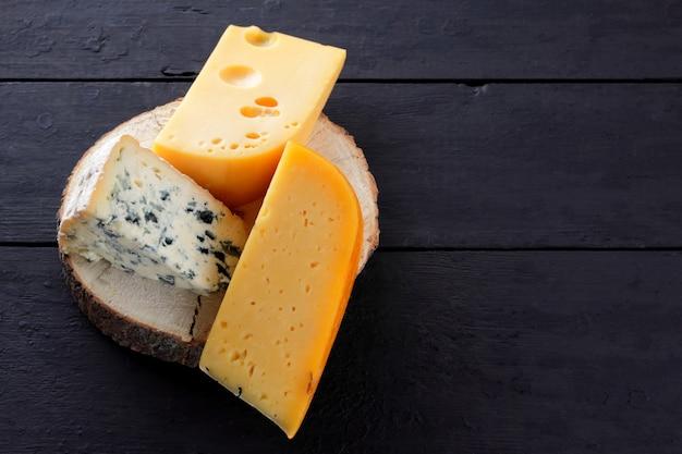 Queso duro y queso azul sobre soporte de madera. diferentes tipos de queso en pizarras negras.