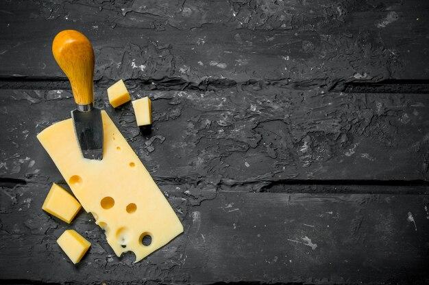 Queso fresco con cuchillo sobre mesa de madera negra.