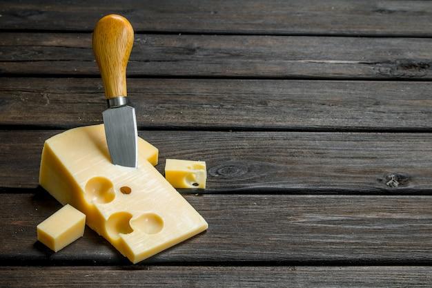 Queso fresco con cuchillo sobre mesa de madera.
