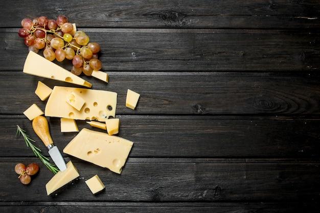 Queso fresco con uvas en mesa de madera.