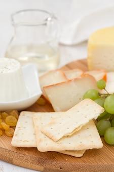 Queso con galletas, uvas y vino blanco en el escritorio de mesa de madera