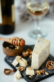 Queso gorgonzola azul italiano sobre una mesa de madera con miel, nueces y vidrio
