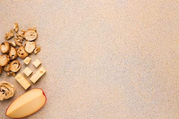 Queso gouda y queso emmental con nuez; rebanada de pan y pasta cruda sobre fondo