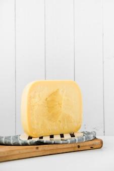 Queso de gouda en la tabla de cortar de madera contra la pared blanca