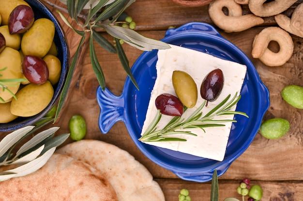 Queso griego feta con tomillo y aceitunas. rama de pan y aceitunas jóvenes