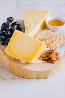 Queso gruyere, uvas, nueces, miel y galleta en tabla de madera sobre mármol