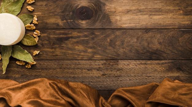 Queso manchego español con hojas secas de laurel y nogal en superficie de madera vieja