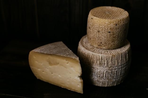 Queso manchego junto a gorgonzola y kravot sobre una tabla de madera oscura. fotografía de queso en clave baja. queso blando natural elaborado con leche de vaca y cabra