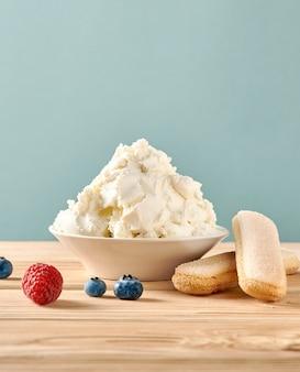 Queso mascarpone, galletas savoiardi y bayas en la mesa de madera. queso crema casero.