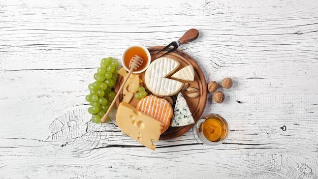 Queso, miel, uva, nueces y copa de vino en tabla de cortar y mesa de madera blanca