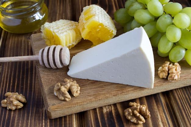 Queso, miel y uvas en la tabla de cortar marrón