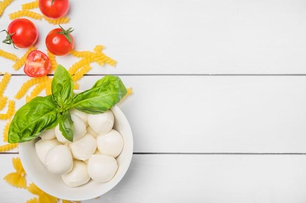 Queso mozzarella italiano con hojas de albahaca; tomate y pasta fusilli sobre tabla de madera blanca