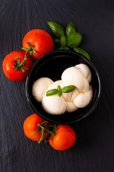 Queso mozzarella orgánico en taza de cerámica negra con tomate y albahaca con espacio de copia