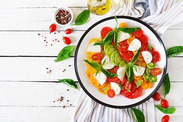 Queso mozzarella, tomate y hojas de hierba de albahaca en plato