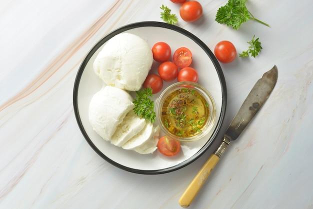 Queso mozzarella y tomates cherry con especias. queso mozzarella hecho en casa.