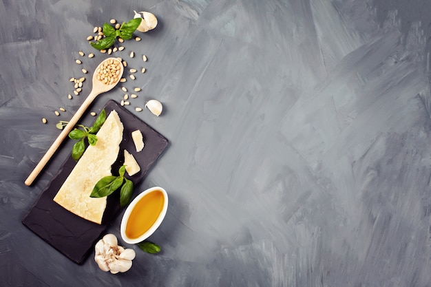 Queso parmesano, aceite de oliva, albahaca, ajo, piñones: ingredientes frescos para cocinar con pesto. concepto de cocina italiana