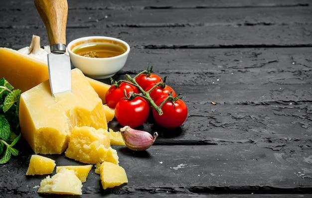 Queso parmesano con tomate, ajo y aceite de oliva. sobre fondo rústico negro.