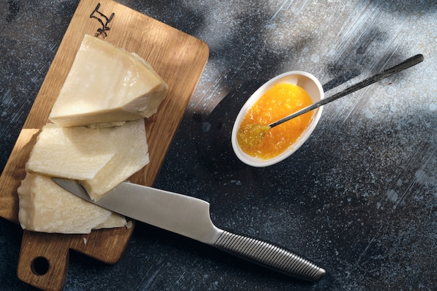 Queso parmigiano en tabla de cortar de madera con bayas de uva
