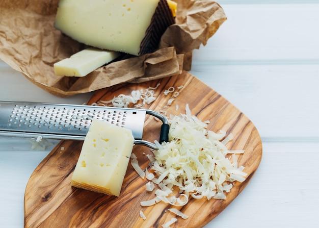 Queso rallado con rallador de queso y trozo de queso en el tablero de la cocina. concepto de cocina.