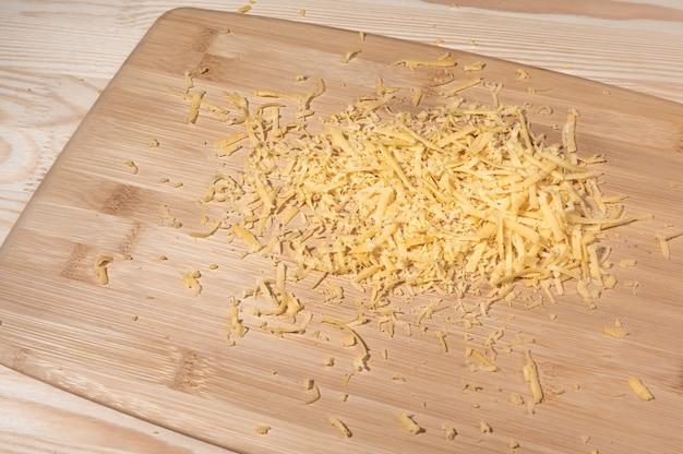 Queso rallado sobre una tabla de cortar de madera. queso rallado sobre la mesa. montón de queso rallado pizza cerrar