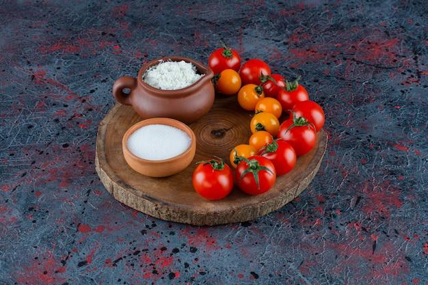 Queso, sal y tomates en una tabla, sobre el fondo de mármol.
