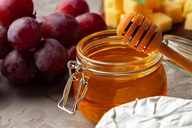 Queso servido con uvas y miel sobre superficie texturizada gris