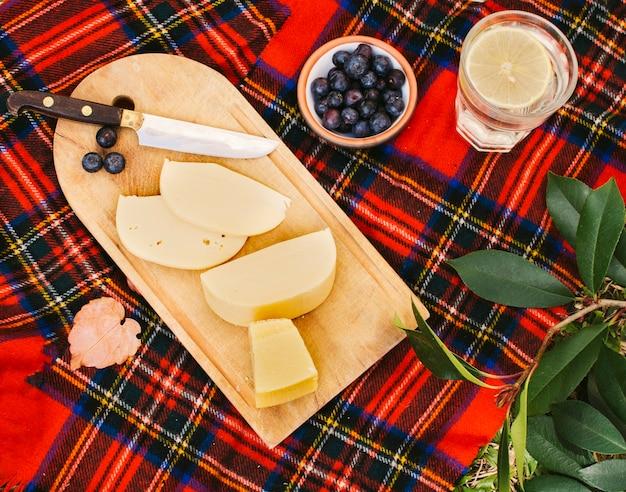 Queso en tabla de cortar de madera para picnic