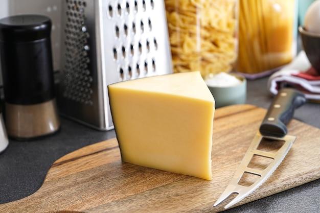 Queso en una tabla de madera con un cuchillo para queso. utensilios de cocina con productos en la superficie de la cocina.
