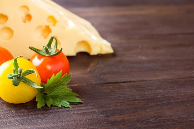 Queso y tomates en madera oscura