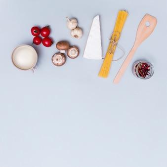 Queso; verduras frescas y salsa blanca para hacer pasta de espagueti en superficie gris