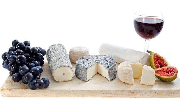 Quesos de cabra, frutas y copa de vino sobre tabla de madera
