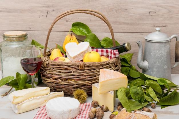 Quesos franceses con una cesta de frutas