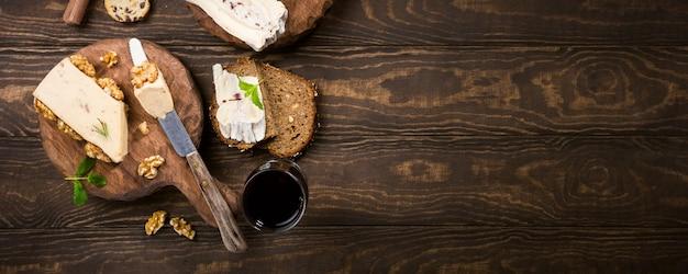 Quesos surtidos sobre plancha de tablas de madera, pan y vino.