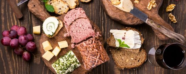 Quesos surtidos en tablas de madera, uvas, pan, vino y paté.