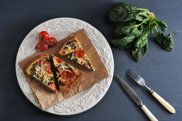 Quiche francesa con huevos, espinacas, tomates y tocino con la receta de un delicioso plato.
