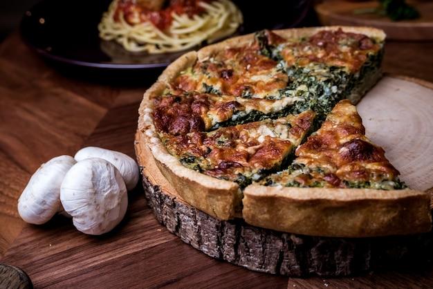 Quiche, una sabrosa tarta abierta con queso de champiñones y espinacas.