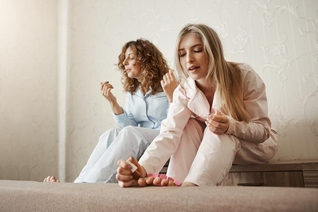 ¿quién necesita salones de belleza cuando puedes hacer uno en casa? retrato de dos mejores amigos sentados en la habitación y pintando las uñas de los pies, vistiendo ropa de dormir y sintiéndose cómodos, teniendo una fiesta femenina