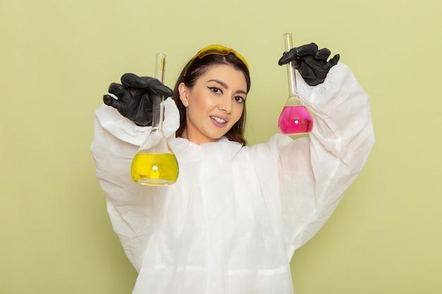 Química femenina de vista frontal en traje de protección especial sosteniendo matraces con diferentes soluciones en la superficie de color verde claro