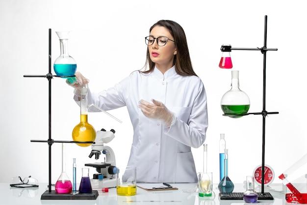 Química de vista frontal en traje médico trabajando con soluciones sobre fondo blanco claro virus de laboratorio covid-ciencia pandémica